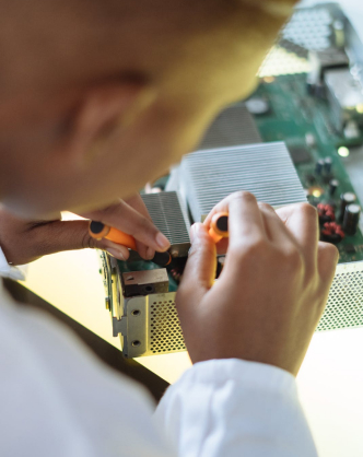 A close up photograph of a man soldering an electrical board